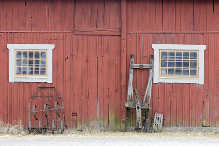 old red barn: Traditional old red barn wall, a window and a sled Stock Photo