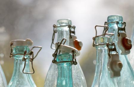 Groupe de dos allumé bleu et transparent vieux façonné bouteilles de verre vides dans une fenêtre, gros plan