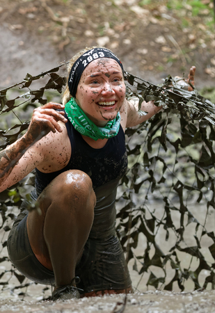 camouflage woman: STOCKHOLM, SWEDEN - MAY 14, 2016: Smiling woman covered with mud crawling under a camouflage net in the obstacle race Tough Viking Event in Sweden, April 14, 2016 Editorial