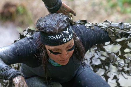 camouflage woman: STOCKHOLM, SWEDEN - MAY 14, 2016: Woman covered with mud crawling under a camouflage net in the obstacle race Tough Viking Event in Sweden, April 14, 2016 Editorial