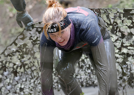camouflage woman: STOCKHOLM, SWEDEN - MAY 14, 2016: Beautiful woman with red hair covered with mud fighting to get out of a camouflage net in the obstacle race Tough Viking Event in Sweden, April 14, 2016 Editorial