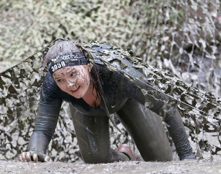 STOCKHOLM, SWEDEN - MAY 14, 2016: Woman covered with mud fighting to get out of a camouflage net in the obstacle race Tough Viking Event in Sweden, April 14, 2016