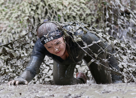 camouflage woman: STOCKHOLM, SWEDEN - MAY 14, 2016: Woman covered with mud fighting to get out of a camouflage net in the obstacle race Tough Viking Event in Sweden, April 14, 2016