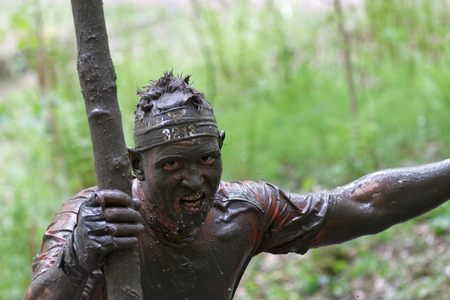 tenacious: STOCKHOLM, SWEDEN - MAY 14, 2016: Angry man covered with mud screaming in the obstacle race Tough Viking Event in Sweden, April 14, 2016