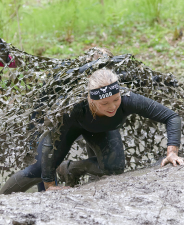 camouflage woman: STOCKHOLM, SWEDEN - MAY 14, 2016: Smiling, crawling, beautiful woman covered with mud crawling up from  a camouflage net in the obstacle race Tough Viking Event in Sweden, April 14, 2016