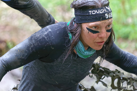 tough woman: STOCKHOLM, SWEDEN - MAY 14, 2016: Woman covered with mud fighting to get out of a camouflage net in the obstacle race Tough Viking Event in Sweden, April 14, 2016