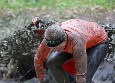 muddy: STOCKHOLM, SWEDEN - MAY 14, 2016: Woman covered with mud fighting to get out of a camouflage net in the obstacle race Tough Viking Event in Sweden, April 14, 2016