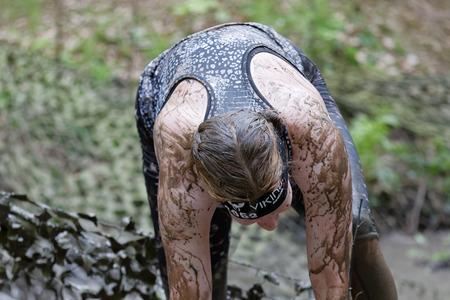 camouflage woman: STOCKHOLM, SWEDEN - MAY 14, 2016: Woman covered with mud bending forward, a camouflage net in the background in the obstacle race Tough Viking Event in Sweden, April 14, 2016 Editorial