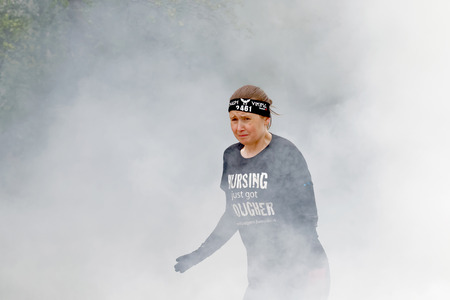woman run: STOCKHOLM, SWEDEN - MAY 14, 2016: Senior woman running through fire and smoke in the obstacle race Tough Viking Event in Sweden, April 14, 2016