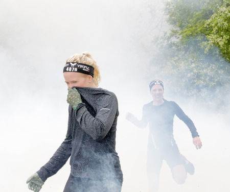tough girl: STOCKHOLM, SWEDEN - MAY 14, 2016: Blonde girl protecting her nose to the smoke in the obstacle race Tough Viking Event in Sweden, April 14, 2016