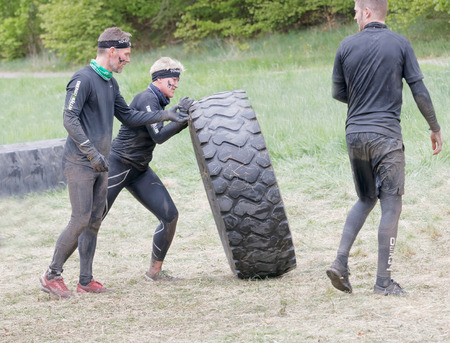 overturn: STOCKHOLM, SWEDEN - MAY 14, 2016: Two men struggling struggling to tip a large tractor tire obstacle in the obstacle race Tough Viking Event in Sweden, April 14, 2016