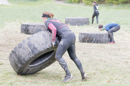 woman run: STOCKHOLM, SWEDEN - MAY 14, 2016: Man and woman struggling to tip a large tractor tire obstacle in the obstacle race Tough Viking Event in Sweden, April 14, 2016