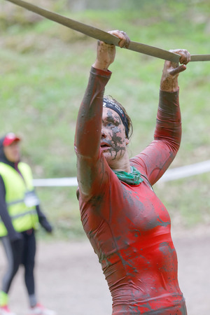 maintain: STOCKHOLM, SWEDEN - MAY 14, 2016: Woman with mud in her face trying to maintain her balance on a slack rope in the obstacle race Tough Viking Event in Sweden, April 14, 2016 Editorial