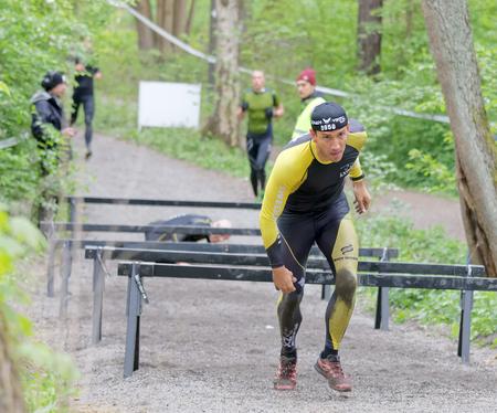 Estocolmo, Suecia - 14 de mayo, 2016: Grupo de personas que luchan arrastran debajo de las barras en la carrera de obstáculos de Viking Tough Evento en Suecia, 14 de Abril, el año 2016