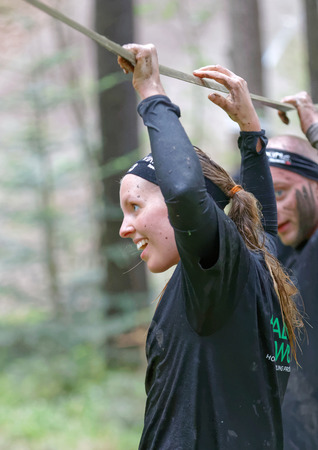 maintain: STOCKHOLM, SWEDEN - MAY 14, 2016: Smiling woman with mud in her face trying to maintain her balance on a slack rope in the obstacle race Tough Viking Event in Sweden, April 14, 2016
