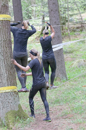 maintain: STOCKHOLM, SWEDEN - MAY 14, 2016: Three woman with mud in their face trying to maintain the balance on a slack rope in the obstacle race Tough Viking Event in Sweden, April 14, 2016