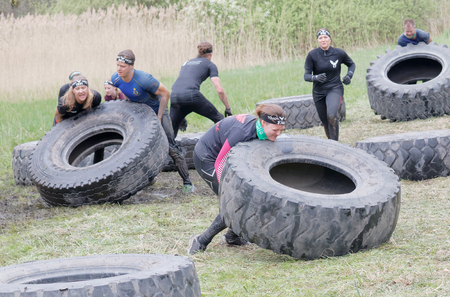 tough woman: STOCKHOLM, SWEDEN - MAY 14, 2016: Group of men and woman struggling to tip a large tractor tire obstacle in the obstacle race Tough Viking Event in Sweden, April 14, 2016