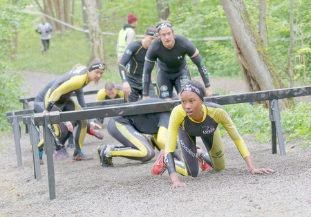 tough woman: STOCKHOLM, SWEDEN - MAY 14, 2016: African woman and competitors crawling under bars in the obstacle race Tough Viking Event in Sweden, April 14, 2016