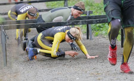 Estocolmo, Suecia - 14 de mayo, 2016: Grupo de personas que luchan arrastran debajo de las barras en la carrera de obstáculos de Viking Tough Evento en Suecia, 14 de Abril, el año 2016 Editorial