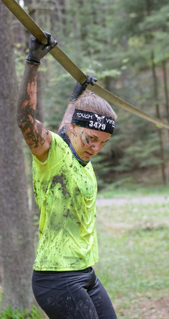 slack: STOCKHOLM, SWEDEN - MAY 14, 2016: Woman with mud in her face trying to maintain her balance on a slack rope in the obstacle race Tough Viking Event in Sweden, April 14, 2016 Editorial