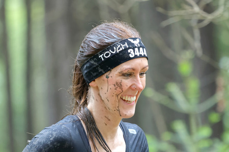tough woman: STOCKHOLM, SWEDEN - MAY 14, 2016: Smiling woman with mud in her face in the obstacle race Tough Viking Event in Sweden, April 14, 2016