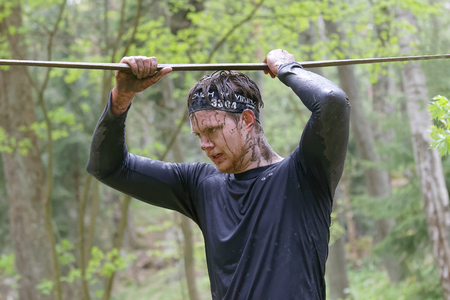 maintain: STOCKHOLM, SWEDEN - MAY 14, 2016: Concentrated man with mud in his face trying to maintain his balance on a slack rope in the obstacle race Tough Viking Event in Sweden, April 14, 2016