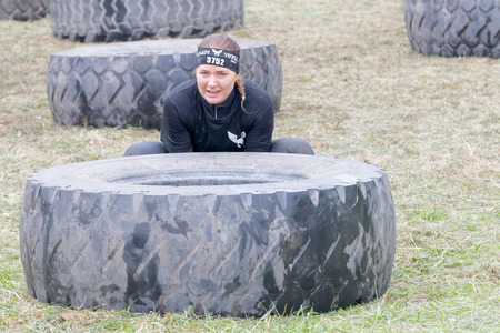 overturn: STOCKHOLM, SWEDEN - MAY 14, 2016: Woman struggling to tip a large tractor tire obstacle in the obstacle race Tough Viking Event in Sweden, April 14, 2016 Editorial