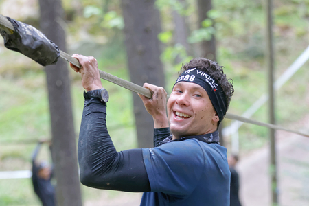 maintain: STOCKHOLM, SWEDEN - MAY 14, 2016: Smiling man trying to maintain his balance on a slack rope in the obstacle race Tough Viking Event in Sweden, April 14, 2016 Editorial