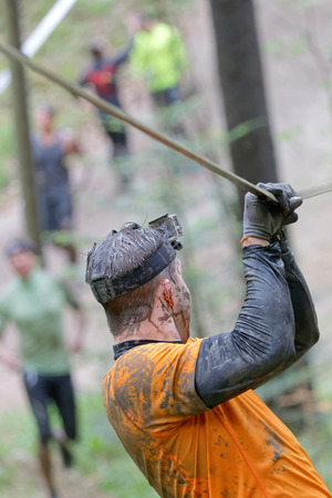 maintain: STOCKHOLM, SWEDEN - MAY 14, 2016: Rear viev of man with mud in his face trying to maintain his balance on a slack rope in the obstacle race Tough Viking Event in Sweden, April 14, 2016