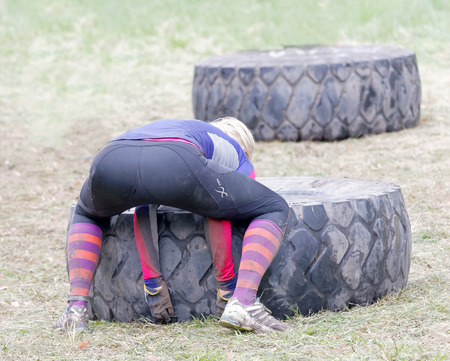 tough woman: STOCKHOLM, SWEDEN - MAY 14, 2016: Rear view of woman struggling to tip a large tractor tire obstacle in the obstacle race Tough Viking Event in Sweden, April 14, 2016