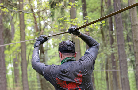 slack: STOCKHOLM, SWEDEN - MAY 14, 2016: Rear view of man with mud in his face trying to maintain his balance on a slack rope in the obstacle race Tough Viking Event in Sweden, April 14, 2016