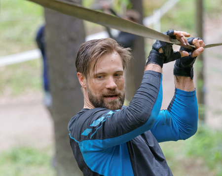 maintain: STOCKHOLM, SWEDEN - MAY 14, 2016: Man trying to maintain his balance on a slack rope in the obstacle race Tough Viking Event in Sweden, April 14, 2016