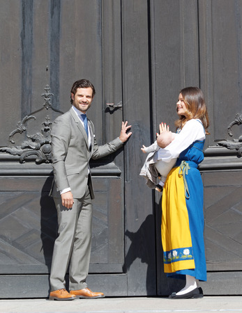 door opening: STOCKHOLM, SWEDEN - JUN 06, 2016: The swedish prince Carl Philip Bernadotte and princess Sofia Hellqvist and prince Alexander opening the door ito  the royal castle during the swedish National day