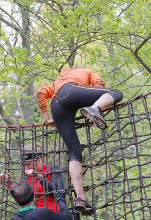 woman run: STOCKHOLM, SWEDEN - MAY 14, 2016: Woman climbing up a net in the obstacle race Tough Viking Event in Sweden, May 14, 2016