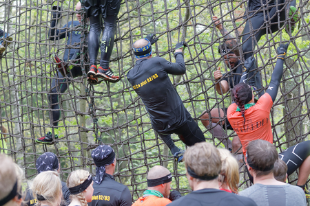 woman run: STOCKHOLM, SWEDEN - MAY 14, 2016: Group of men and woman climbing up a net in the obstacle race Tough Viking Event in Sweden, May 14, 2016