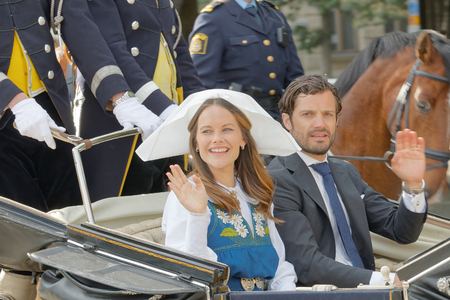 carl: STOCKHOLM, SWEDEN - JUN 06, 2016: The swedish princess and prince Sofia and Carl Philip Bernadotte smiling and waiving to the audience from the royal coach on their way to celebrate the swedish national day.