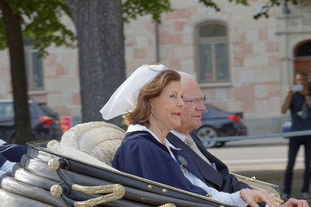 gustaf: STOCKHOLM, SWEDEN - JUN 06, 2016: The swedish queen and king Silvia and Carl Gustaf Bernadotte waiving to the audience from the royal coach on their way to celebrate the swedish national day. Editorial
