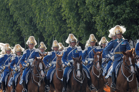 STOCKHOLM - JUN 06, 2016: The Royal guards in blue uniforms on the horse back protecting the swedish royal family on their way to celebrate the swedish national day