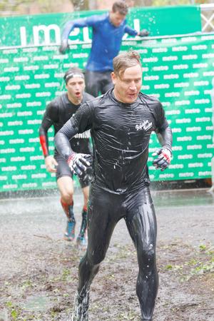 Estocolmo, Suecia - 14 de mayo, 2016: Hombres saltando de un tanque de agua enfriada con hielo y se ejecuta en el barro en el obstáculo de cubitos de hielo en la carrera de obstáculos de Viking Tough Evento en Suecia, 14 de Mayo, el año 2016 Editorial