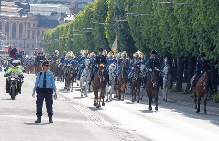 STOCKHOLM - JUN 06, 2016: The Royal guards on the horse back and the police protecting the swedish royal family on their way to celebrate the swedish national day