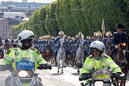 STOCKHOLM - JUN 06, 2016: The Royal guards on the horse back and the motorcycle police protecting the swedish royal family on their way to celebrate the swedish national day