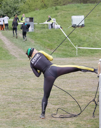 woman run: STOCKHOLM, SWEDEN - MAY 14, 2016: Woman fighting to hoist a heavy kettlebell using a rope in the Thor Strength obstacle in the obstacle race Tough Viking Event in Sweden, May 14, 2016