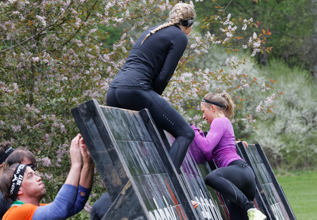 woman run: STOCKHOLM, SWEDEN - MAY 14, 2016: Women climbing over a plank obstracle in the obstacle race Tough Viking Event in Sweden, May 14, 2016