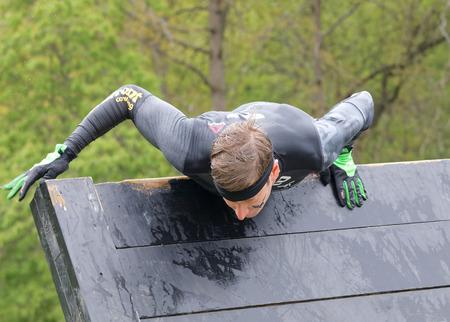 Estocolmo, Suecia - 14 de mayo, 2016: Los hombres que sube sobre una obstracle viga que está en la carrera de obstáculos de Viking Tough Evento en Suecia, 14 de Mayo, el año 2016