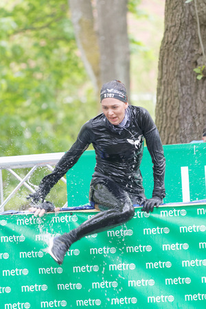 person woman: STOCKHOLM, SWEDEN - MAY 14, 2016: Woman jumping out of a tank of ice cold water in the Ice cube obstacle in the obstacle race Tough Viking Event in Sweden, May 14, 2016 Editorial