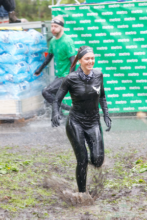woman run: STOCKHOLM, SWEDEN - MAY 14, 2016: Woman jumping out of a tank of ice cold water and running in the mud  in the Ice cube obstacle in the obstacle race Tough Viking Event in Sweden, May 14, 2016