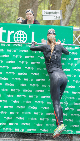 woman run: STOCKHOLM, SWEDEN - MAY 14, 2016: Woman jumping out of a tank of ice cold water in the Ice cube obstacle in the obstacle race Tough Viking Event in Sweden, May 14, 2016 Editorial