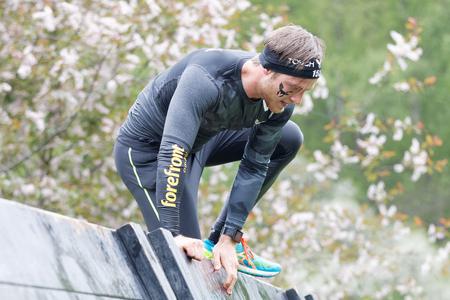 Estocolmo, Suecia - 14 de mayo, 2016: El hombre sube sobre una obstracle viga que está en la carrera de obstáculos de Viking Tough Evento en Suecia, 14 de Mayo, el año 2016