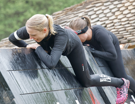 woman run: STOCKHOLM, SWEDEN - MAY 14, 2016: Smiling women climbing over a plank obstracle in the obstacle race Tough Viking Event in Sweden, May 14, 2016