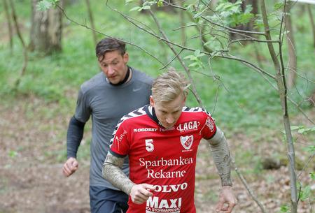 agachado: Estocolmo, Suecia - 14 de mayo, 2016: Dos hombres que se ejecutan en el bosque agach�ndose para evitar una rama en la carrera de obst�culos de Viking Tough Evento en Suecia, 14 de Mayo, el a�o 2016 Editorial